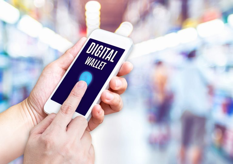 Hand holding mobile phone with Digital Wallet word with blurred